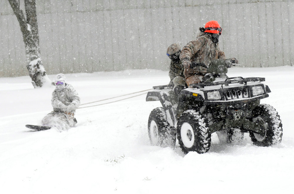 . Dane Eagle and Remington Eagle pull Dalton Eagle on a sled behind the ATV Dane is driving during a snow storm Wednesday, Dec. 26, 2012 on in Ashland, Ohio. (AP Photo/Ashland Times-Gazette, Tom E. Puskar)