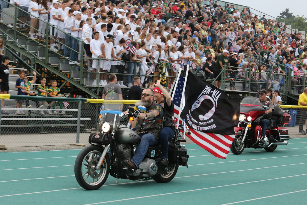 . David Schneider - The Morning Journal<br> The American Legion Riders drive around the track at Amherst\'s stadium before the game. They were part of the POW-MIA seat dedication in the home bleachers.