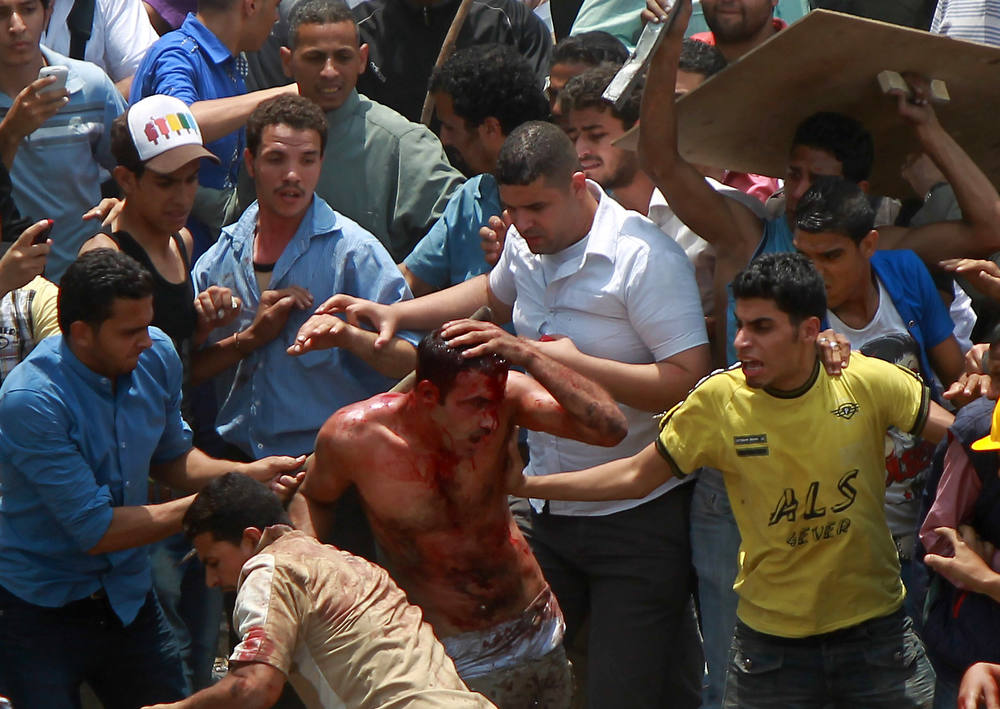 . Egyptian protesters beat a man who they accused of attacking them in the Abbassiya district in Cairo on May 2, 2012. At least 12 people were killed when attackers stormed an anti-military protest near the defence ministry in Cairo, medics and a security official said. The fate of the man is unknown. AFP PHOTO/KHALED  DESOUKI/AFP/Getty Images