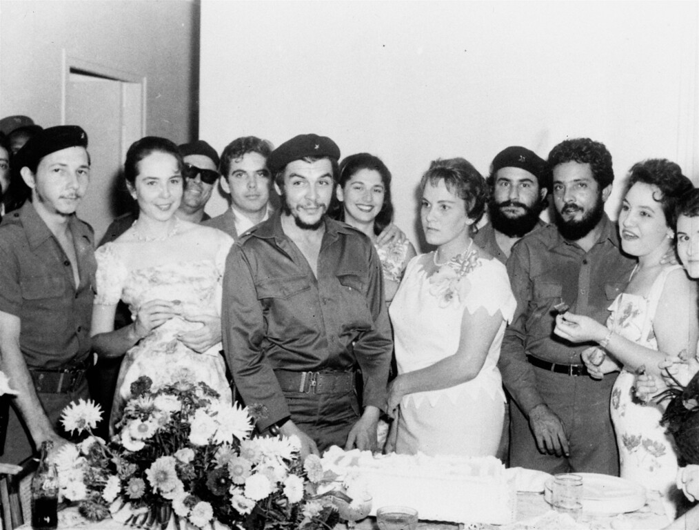 ". Major Ernesto ""Che\"" Guevara, 34, Argentine hero of the Cuban revolution, and his bride Aleida, stand before the wedding cake following their marriage at a civil ceremony at La Cabana Military fortress, March 23, 1959.  At the extreme left is Maj. Raul Castro, commander in chief of the armed forces and brother of Prime Minister Fidel Castro.  Next to Major Castro stands his wife, Vilma Esping. (AP Photo)"