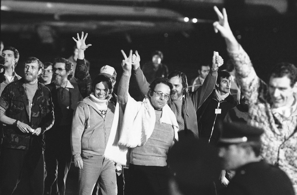 . A group of unidentified American hostages give the victory sign as they emerge from an Algerian aircraft in Algiers after their flight from Teheran where they had been held captive for 444 days in Iran, Jan. 21, 1981.  (AP Photo/David Caulkin)
