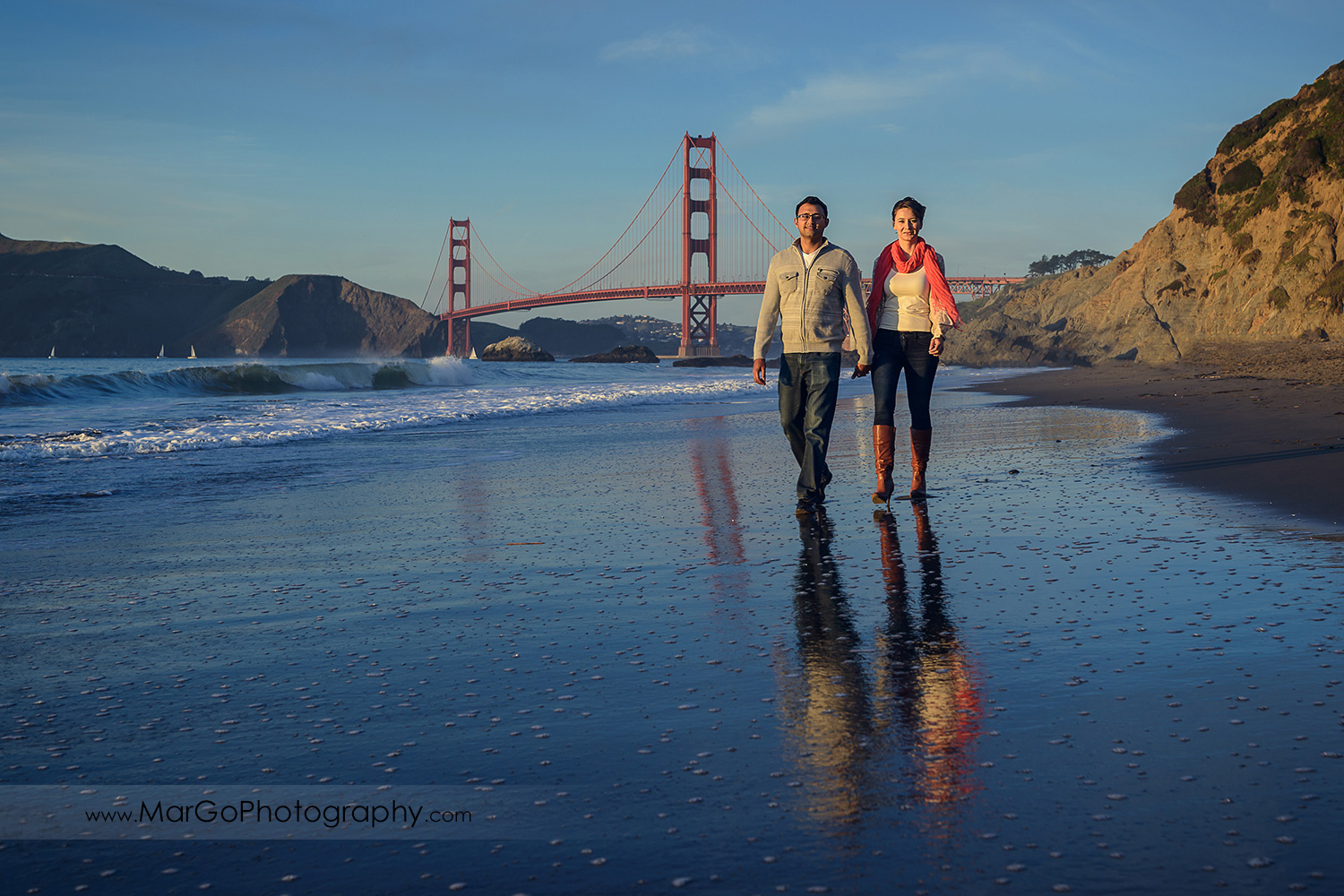 man and woman in grey sweater and jeans holding hand and walking on the Baker Beach with Golden Gate Bridge in background during San Francisco engagement session