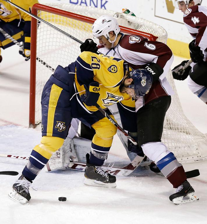 . Nashville Predators forward Paul Gaustad (28) battles Colorado Avalanche defenseman Erik Johnson (6) for the puck in the third period of an NHL hockey game, Saturday, Jan. 18, 2014, in Nashville, Tenn. (AP Photo/Mark Humphrey)