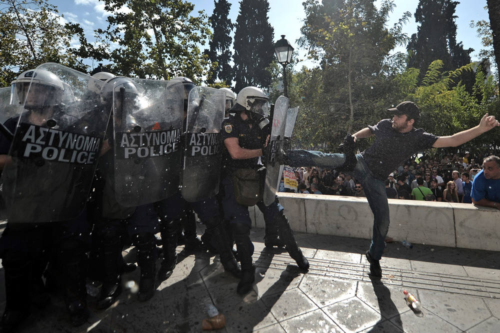 Description of . A demonstrator clashes with riot police during a 24-hour strike in Athens on October 18, 2012. Greek riot police fired tear gas to disperse protesters at an anti-austerity rally in Athens held during a national general strike as EU leaders were to tackle the eurozone crisis at a summit. The protesters had broken through a police line outside luxury hotels on central Syntagma Square and scattered groups of youths later attacked police with stones and firebombs, an AFP reporter said. AFP PHOTO / ARIS  MESSINIS/AFP/Getty Images