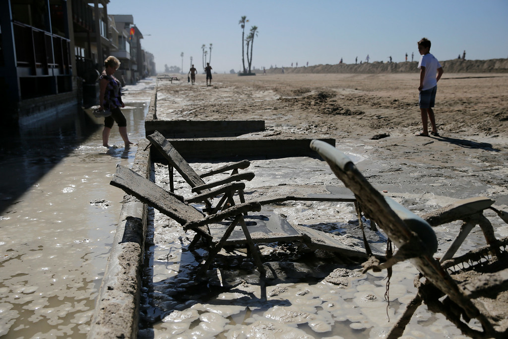 . Beach chairs are covered in mud in the flooded beachfront area on Wednesday, Aug. 27, 2014, in Seal Beach, Calif. (AP Photo/Jae C. Hong)