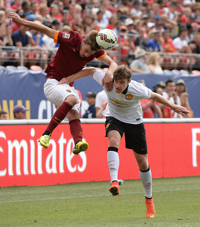 . AS Roma midfielder Mihai Balasa, left, got his head on the ball in front of Manchester United defender Michael Keane, right, in the second half. Manchester United defeated AS Roma 3-2 in an exhibition soccer game at Sports Authority Field in Denver Saturday afternoon, July 27, 2014. Photo by Karl Gehring/The Denver Post