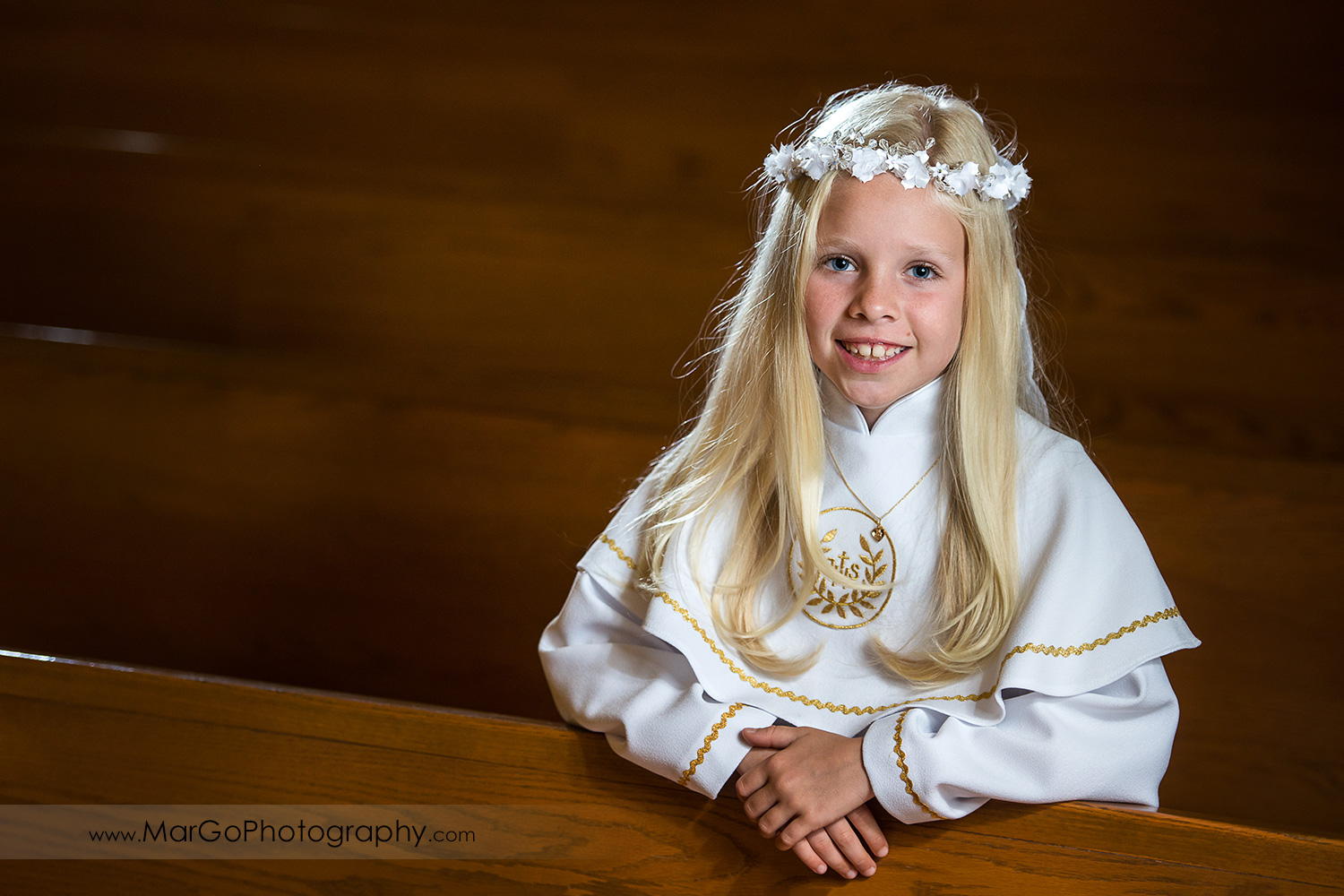 first communion girl in white alb in wooden San Jose church pews