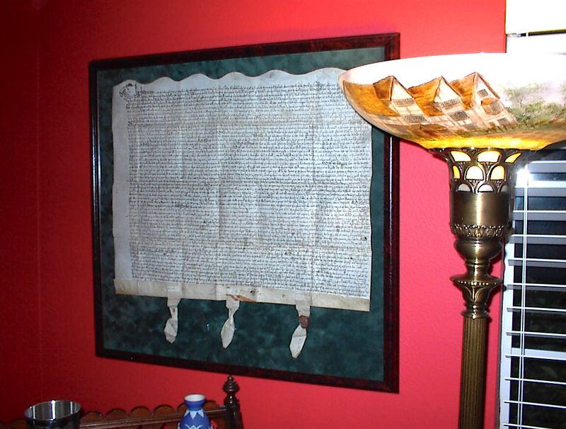 A rare 16th century English indenture contract with wax seals, executed during the reign of Elizabeth I. Appropriate to the age of the document, a handpainted rendition of Shakespeare's birthplace in Stratford Upon Avon is depicted on the shade of the antique floor lamp in the foreground.