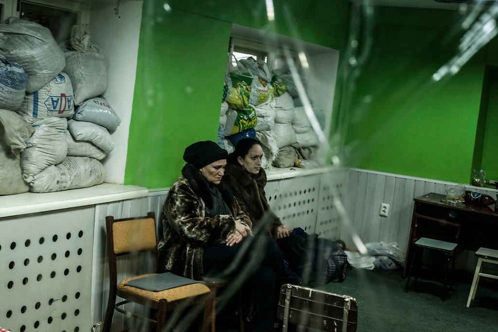 . Ukrainian women sit in a shelter during a exchange of artillery fire between DNR forces and the Ukrainian Army in the Voroshilovsky area, center of Donetsk, Ukraine. Sunday, Jan. 18, 2015. The separatist stronghold, Donetsk, was shaken by intense outgoing and incoming artillery fire as a bitter battle raged for control over the city\'s airport. Streets in the city, which was home to 1 million people before unrest erupted in spring, were completely deserted and the windows of apartments in the center rattled from incessant rocket and mortar fire. (AP Photo/Manu Brabo)