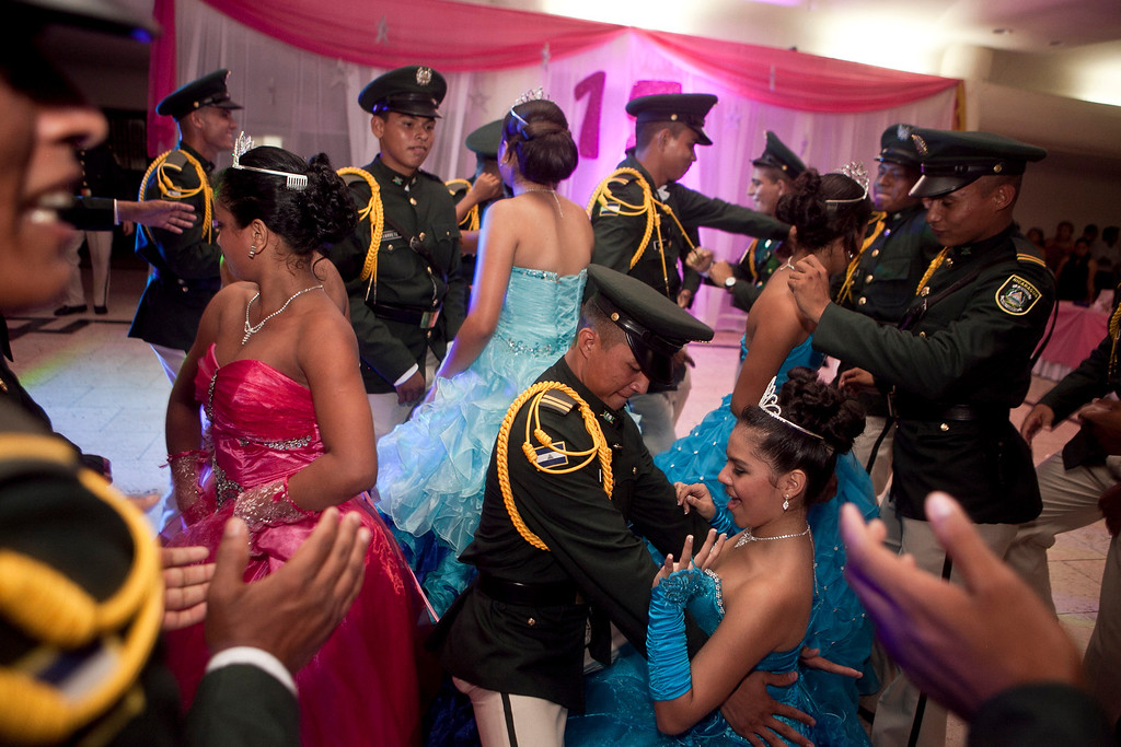 """. In this Saturday, Sept. 21, 2013, Nicaraguan girls dance with army cadets during a \""""quinceanera\"""" party in Managua, Nicaragua. Nicaraguaís Association of Mothers and Fathers of Children with Cancer and Leukemia put on for the fifith year, a the traditional coming out party for the girls from poor, rural families, teens who have the added burden of dealing with cancer. This yearís party feted 37 girls between ages 14 and 16. (AP Photo/Esteban Felix)"""