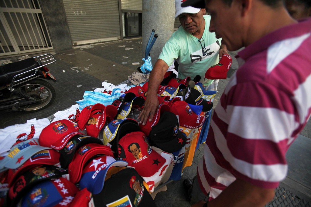 ". A street vendor sells baseball caps decorated with images of Venezuela\'s late President Hugo Chavez, and T-shirts with a the words in Spanish ""I am Chavez\"" in Caracas, Venezuela, Monday, March 11, 2013. At Caracas\'s choked Bolivar Plaza, a favorite hangout for the late president\'s supporters, shoppers can find virtually anything Chavez-related the mind can dream up. (AP Photo/Fernando Llano)"