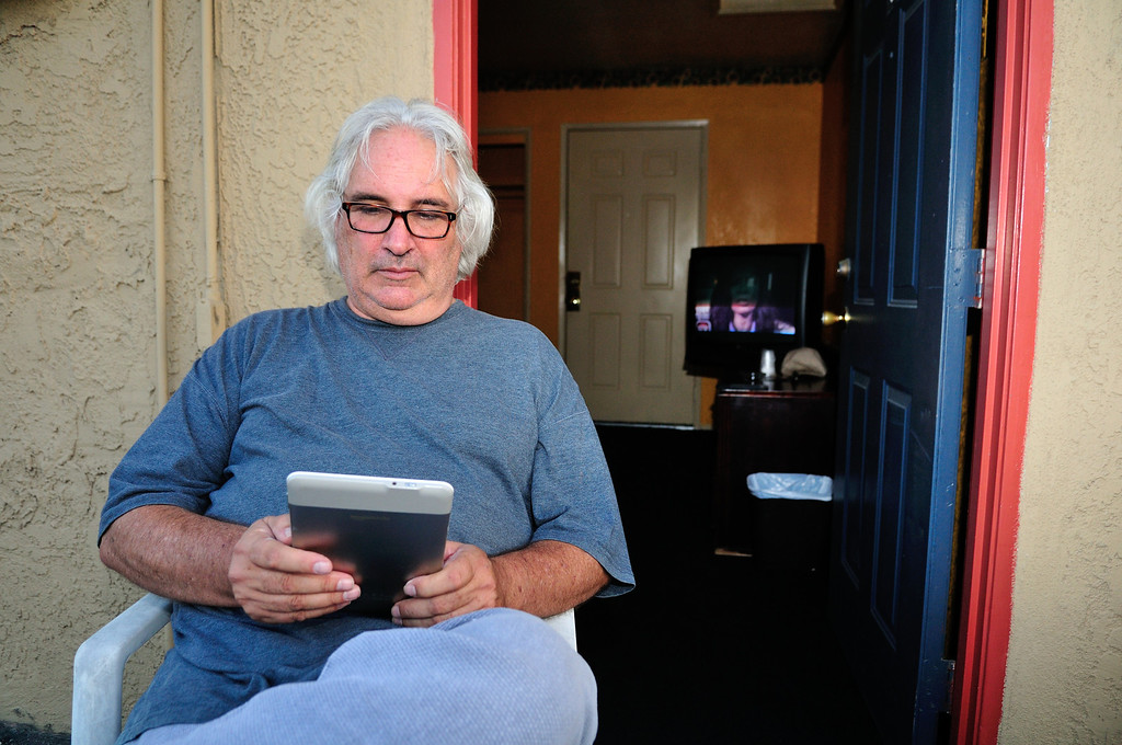 . Tim Grobaty reads his Kindle outside his room at the El Capitan Motor Inn.Photo by Thomas Wasper for the Press Telegram