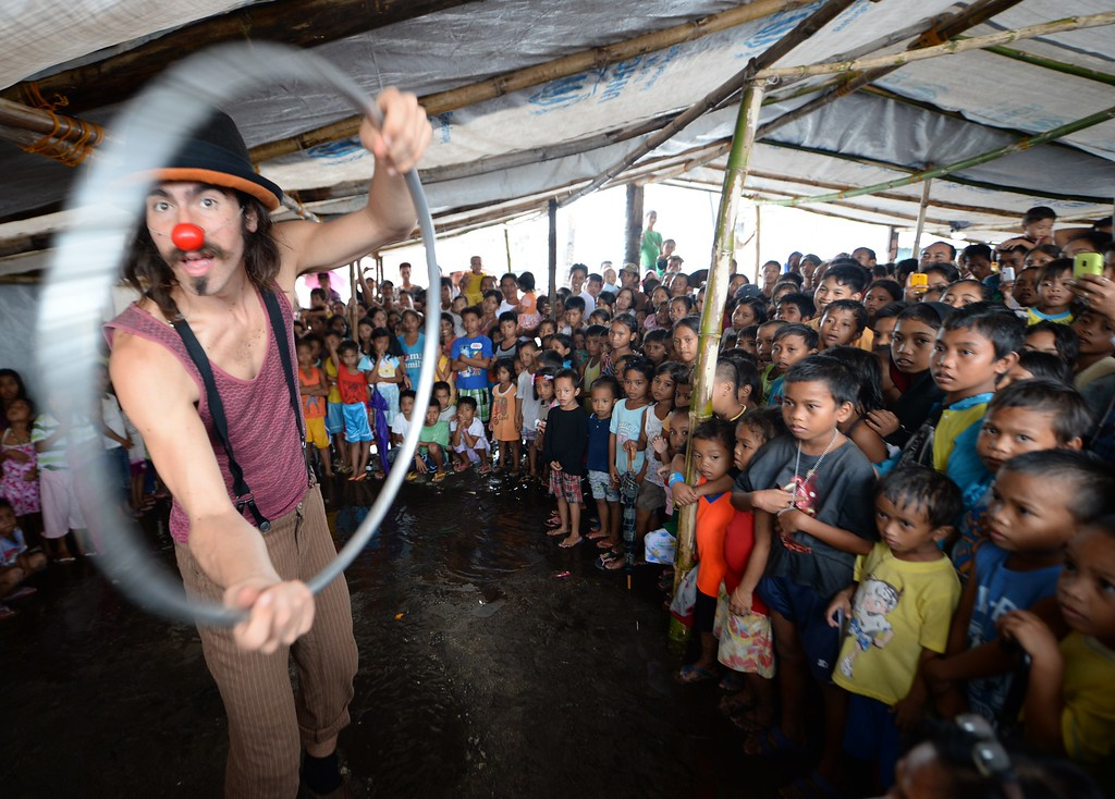 . A member of Clowns Without Borders performs in front of young survivors of the super Typhoon Haiyan as part of recovery work by Plan international at a tent city in Tacloban city, Leyte province, on December 25, 2013.  Survivors of the Philippines\' deadliest typhoon spent a gloomy Christmas Day surrounded by mud December 25 as heavy rain drove many inside their flimsy shelters, dampening efforts to retain some holiday cheer in the deeply devout nation.    AFP PHOTO/TED ALJIBETED ALJIBE/AFP/Getty Images