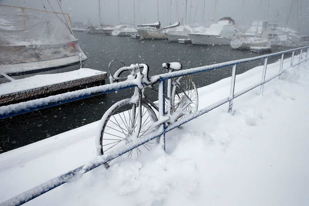 . A bicycle is chained to a railing at the Boston Harbor Shipyard and Marina in Boston, Tuesday, March 13, 2018. Boston finds itself in the bullseye of the third nor\'easter in two weeks, with forecasters warning of up to 18 inches of snow and 2 feet or more to the south. (AP Photo/Michael Dwyer)