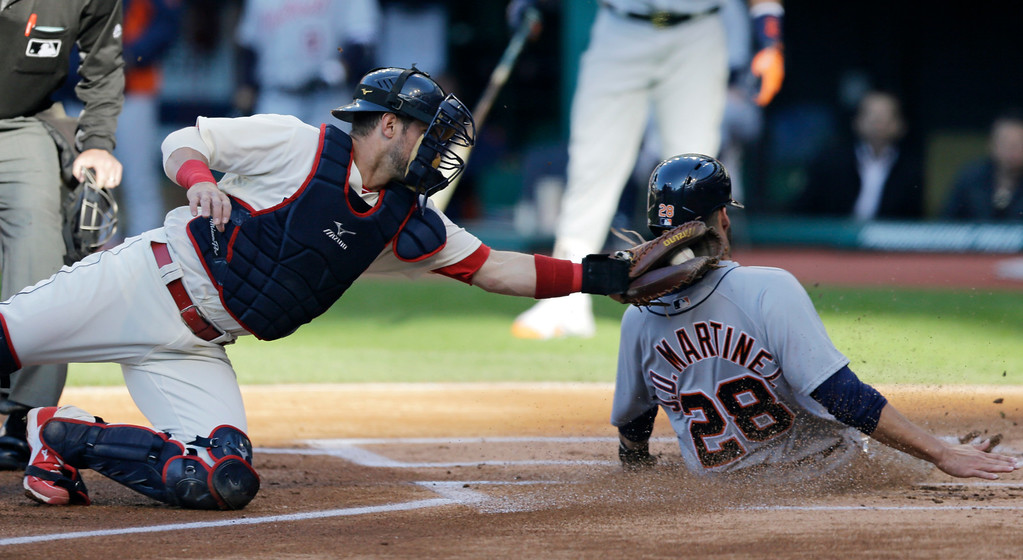 . Cleveland Indians\' Yan Gomes tags out Detroit Tigers\' J.D. Martinez at home plate in the first inning of a baseball game, Tuesday, May 3, 2016, in Cleveland. (AP Photo/Tony Dejak)