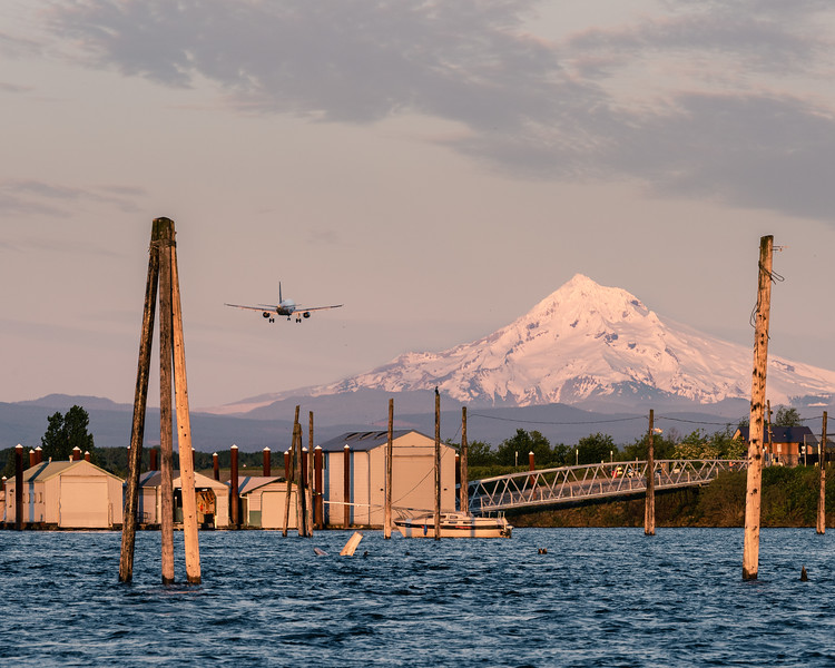 PDX airport is by the River, airplane landing at sunset.  Mt Hood is approx 50 miles distant.