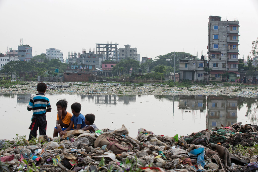 ". Bangladeshi children sit on garbage piled up by the river Buriganga in Hazaribagh area in Dhaka, Bangladesh, Monday, June 4, 2018. The theme for this year\'s World Environment Day, marked on June 5, is ""Beat Plastic Pollution.\"" (AP Photo/A.M. Ahad)"