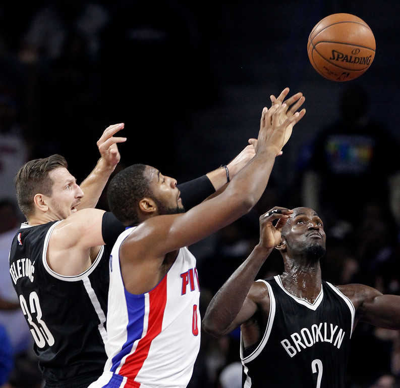 . Detroit Pistons\' Andre Drummond (0) tries to grab a loose ball against Brookyn Nets\' Mirza Teletovic (33) and Kevin Garnett (2) during the first half of an NBA basketball game Saturday, Nov. 1, 2014, in Auburn Hills, Mich. (AP Photo/Duane Burleson)