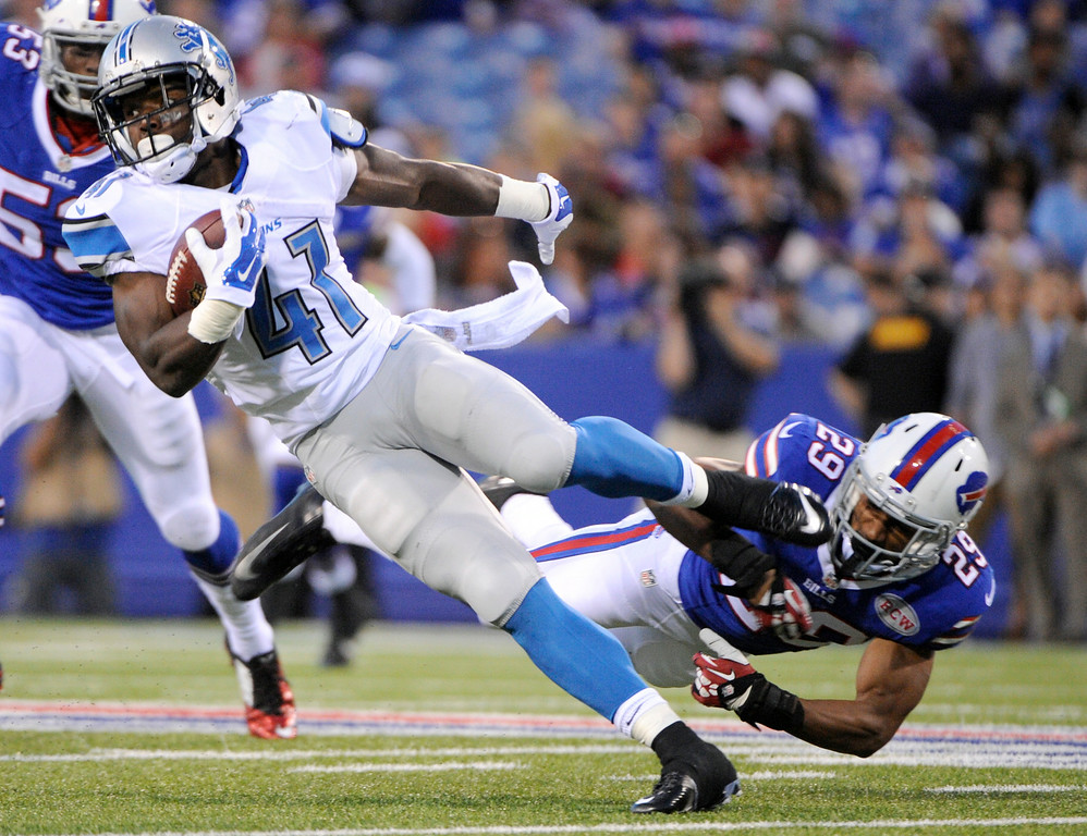 . Detroit Lions running back Theo Riddick (41) is tripped up by Buffalo Bills cornerback Ross Cockrell (29) during the first half of a preseason NFL football game, Thursday, Aug. 28, 2014, in Orchard Park, N.Y. (AP Photo/Gary Wiepert)