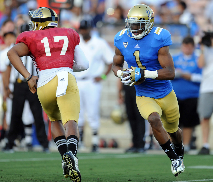 . UCLA quarterback Brett Hundley (17) hands-off to wide receiver Shaquelle Evans (1) during the football spring showcase college football game in the Rose Bowl on Saturday, April 27, 2013 in Pasadena, Calif.    (Keith Birmingham Pasadena Star-News)