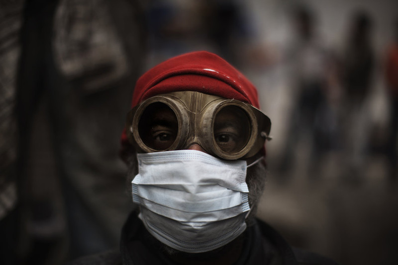 . An Egyptian demonstrator uses goggles and a protective mask against tear gas fired by riot police during confrontations outside Cairo\'s security headquarters on February 6, 2012, as clashes continued in the Egyptian capital in the wake of deadly football violence and amid calls by activists for civil disobedience in Egypt.   MARCO LONGARI/AFP/Getty Images