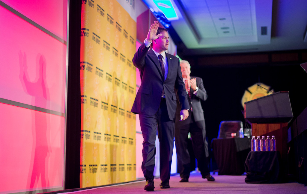 . Sen. Marco Rubio, R-Fla. waves as he walks off stage after speaking at the International Association of Firefighters (IAFF) Legislative Conference and Presidential Forum in Washington, Tuesday, March 10, 2015. Behind Rubio is International Association of Firefighters (IAFF) President Harold A. Schaitberger, right. (AP Photo/Pablo Martinez Monsivais)