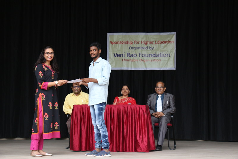 Ms. Nikhila Pinjala, Trustee- Veni Rao Foundation giving Scholarship cheque to Mr. Prem Kumar.JPG