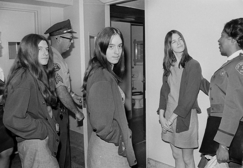 . Dressed in jail denims, three women who are co-defendants with Charles M. Manson in the Sharon Tate murder trial, walk toward a Los Angeles courtroom, Aug. 6, 1979. The women are on their way to listen to further cross-examination of Linda Kasabian, the state\'s principal witness against them. Left to right are: Leslie Van Houten, Susan Atkins and Patricia Krenwinkel. (AP Photo/Wally Fong)