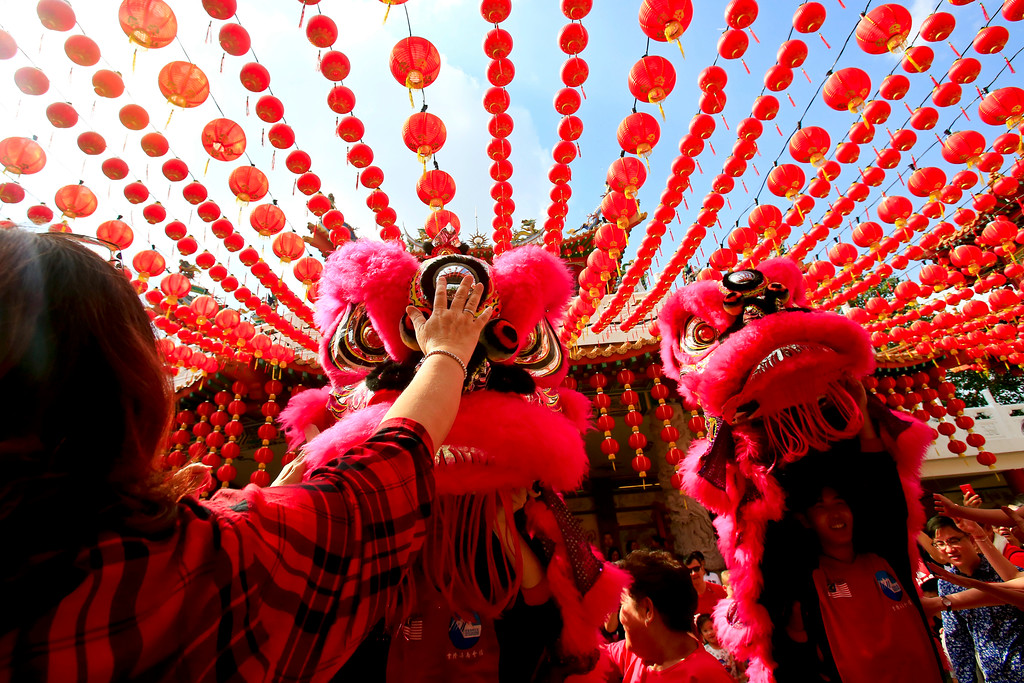 . Temple visitors play with the lion dance troupe during its performance on the first day of Chinese Lunar New Year at a temple in Kuala Lumpur, Malaysia, Friday, Feb. 16, 2018. The celebration marks the Year of the Dog in the Chinese calendar. (AP Photo/Sadiq Asyraf)
