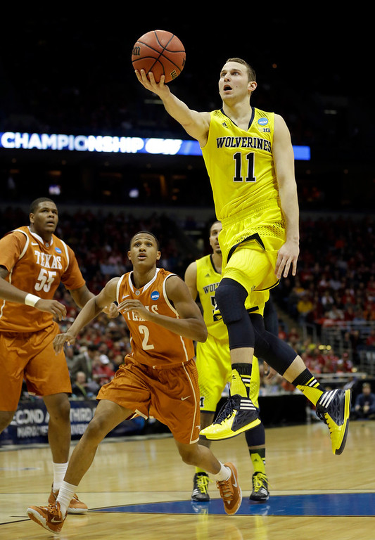 . Michigan guard Nik Stauskas (11) drives to the basket during the first half of a third-round game against the Texas of the NCAA college basketball tournament Saturday, March 22, 2014, in Milwaukee. (AP Photo/Morry Gash)