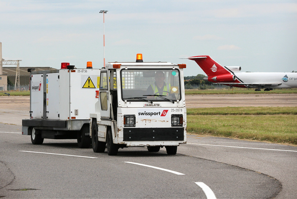 "This swissport tug is towing a GPU (Ground Power Unit) The tug is produced by the US Company ""Charlatte"", this particular example being the T-135 AC Tow Tractor. It is powered by a 20hp AC electric motor giving a top speed of 15.5mph and a drawbar capacity of 3500lb.<br /> By Clive Featherstone."