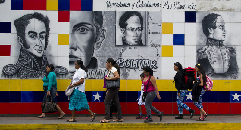 . People walk past a mural of Venezuelan Liberator Simon Bolivar in San Antonio, in the border state of Tachira, Venezuela, on February 25, 2014. Angry Venezuelan students geared up to stage a fresh rally on Tuesday, the latest in three weeks of anti-government protests that have left at least 14 people dead. (LUIS ROBAYO/AFP/Getty Images)