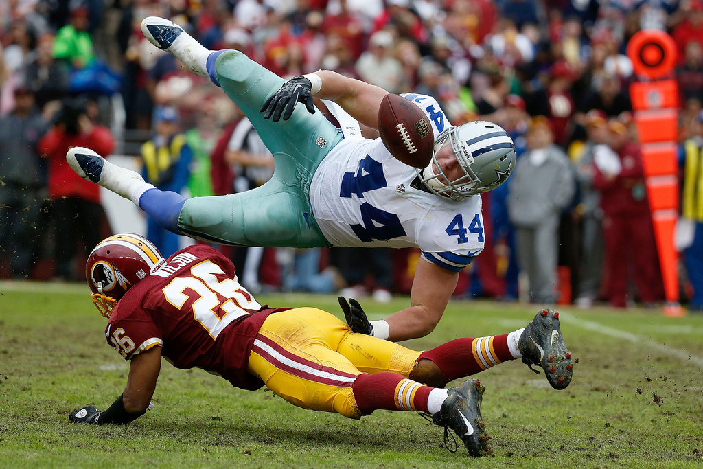 . Dallas Cowboys fullback Tyler Clutts loses control of the ball on a hit from Washington Redskins cornerback Josh Wilson during the second half of an NFL football game in Landover, Md., Sunday, Dec. 22, 2013. The Redskins recovered the fumble. The Cowboys defeated the Redskins 24-23. (AP Photo/Alex Brandon)