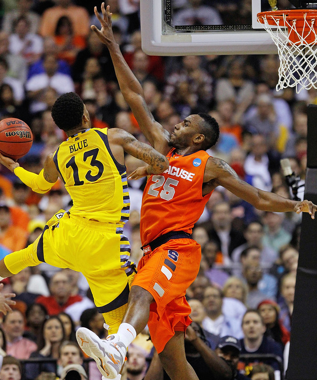 . Marquette guard Vander Blue (13) shoots as Syracuse forward Rakeem Christmas (25) defends during the second half of the East Regional final in the NCAA men\'s college basketball tournament, Saturday, March 30, 2013, in Washington. (AP Photo/Pablo Martinez Monsivais)