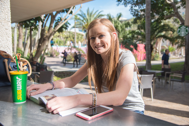 Student Payton Bostick studies for her Psychology class while enjoying the weather at the Island University.