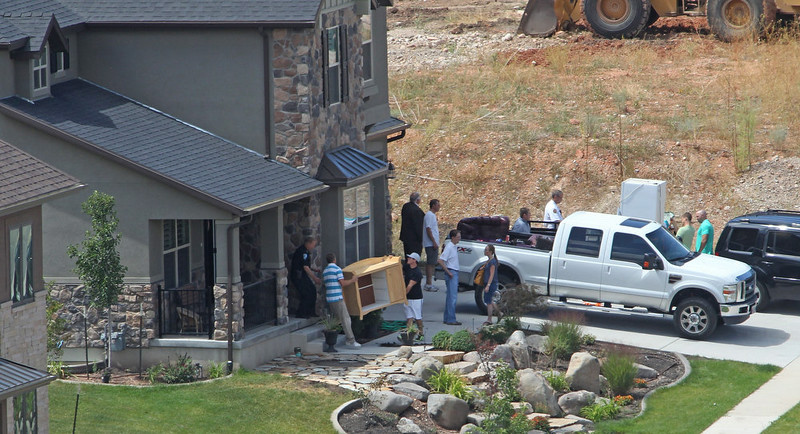 . A home owner evacuates his home following a landslide in a hillside community of North Salt Lake, Utah, Tuesday, Aug. 5, 2014. One home was destroyed and 27 others were evacuated after a landslide early Tuesday struck an upscale suburban Salt Lake City community, where officials had worried for nearly a year about cracked soil on the hillside above the houses. (AP Photo/Rick Bowmer)
