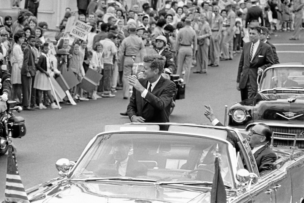 . President John F. Kennedy waves from his car during a parade through the streets of San Diego, June 6, 1963 en route to San Diego State College where he received an honorary degree. (AP Photo)