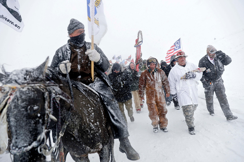 . Military veterans and Native American tribal elders march to a closed bridge outside the Oceti Sakowin camp where people have gathered to protest the Dakota Access oil pipeline in Cannon Ball, N.D., Monday, Dec. 5, 2016. (AP Photo/David Goldman)