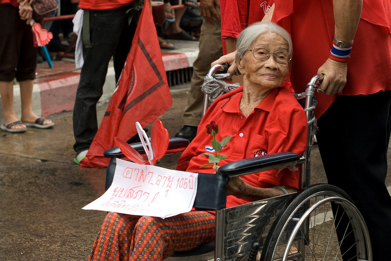Woman on wheelchair holds out flower and signs during Red Shirt Protest