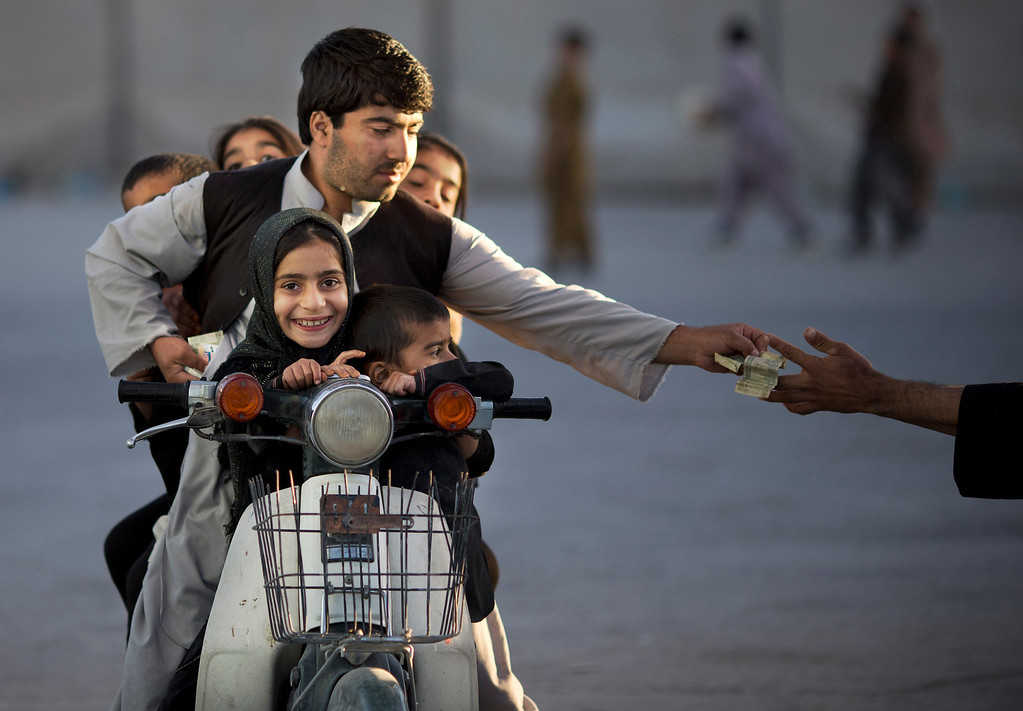 . In this Friday, Nov. 1, 2013 file photo made by Associated Press photographer Anja Niedringhaus, an Afghan man with his five children on his motorbike pays money to enter a park in Kandahar, southern Afghanistan.  (AP Photo/Anja Niedringhaus, File)