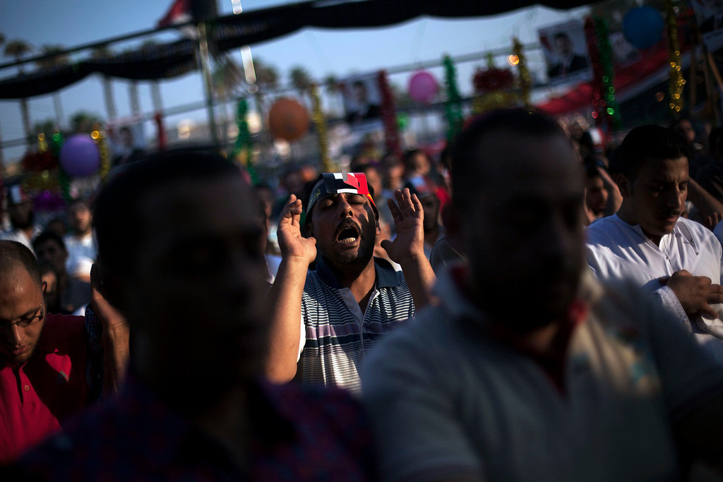""". Supporters of Egypt\'s ousted President Mohammed Morsi pray during the celebration of the \""""Eid al-Fitr\"""" holiday (end of Ramadan) near Cairo University in Giza, Egypt, Thursday, Aug. 8, 2013. This year\'s holiday is overshadowed by the deep divisions in Egypt, with the interim government planning to celebrate the feast with outdoor prayers and protests in town center squares and Morsi\'s supporters marking the holiday with their own protests and prayers, including at the two major sit-ins by the Islamists in Cairo. (AP Photo/Manu Brabo)"""
