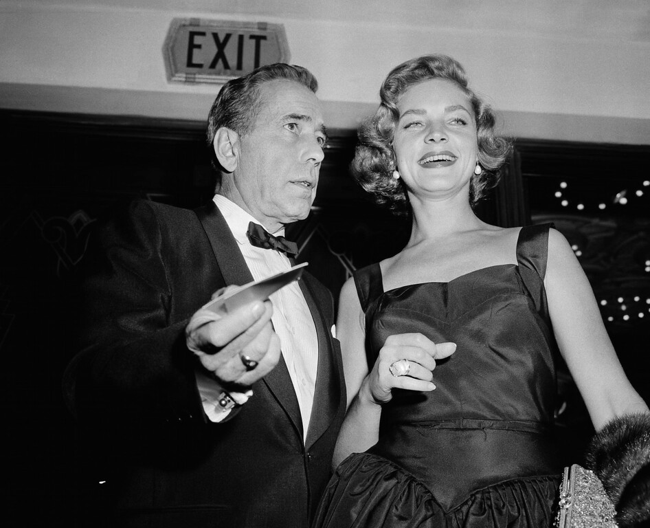 ". FILE - This Oct. 12, 1955 file photo shows actors Humphrey Bogart, left, and his wife, Lauren Bacall at the premiere of ""The Desperate Hours,\"" in Los Angeles. Bacall, the sultry-voiced actress and Humphrey Bogart�s partner off and on the screen, died Tuesday, Aug. 12, 2014 in New York. She was 89. (AP Photo/Harold Filan, FIle)"