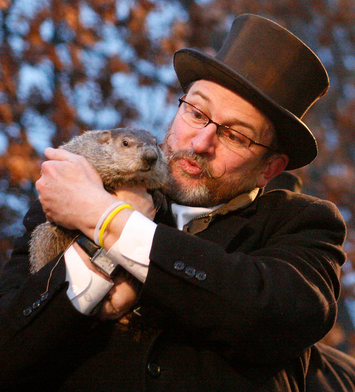 . Punxsutawney Phil, left,  is held by Ben Hughes after emerging from his burrow on Gobblers Knob in Punxsutawney, Pa., to see his shadow and forecast six more weeks of winter weather Tuesday, Feb. 2, 2010.  (AP Photo/Gene J. Puskar)