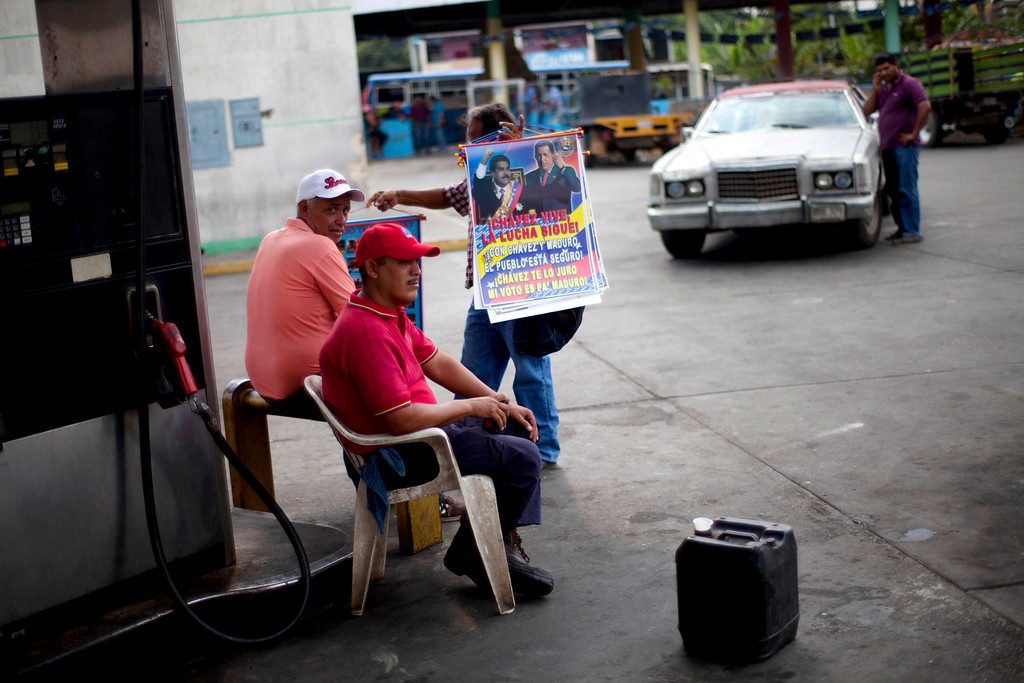 . In this April 8, 2013 photo, street vendor Jose Gonzalez, 62, tries to persuade gas stations workers to buy some posters featuring Venezuela\'s late President Hugo Chavez and acting President Nicolas Maduro, in Tacarigua, Venezuela. Outside Venezuela\'s capital, power outages, food shortages and unfinished projects abound; important factors heading into Sunday\'s election to replace Chavez, who died last month after a long battle with cancer.  Polls show that support for Maduro, Chavez\'s hand-picked successor, may be eroding and constant power outages are a testament to the neglect many Venezuelans consider inexcusable in this major oil-producing state. (AP Photo/Ramon Espinosa)