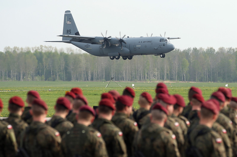 . Members of a Polish paratrooper unit watch as a U.S. Air Force plane ferrying men and equipment of the U.S. Army 173rd Airborne Brigade lands at a Polish air force base on April 23, 2014 in Swidwin, Poland. Approximately 150 U.S. troops, as well as another 450 destined for the three Baltic states in coming days, will participate in bilateral military exercises over the coming weeks in a sign of commitment among NATO members. Tensions are rising in eastern Ukraine between Russian separatists and Ukrainian authorities and NATO is seeking to reassure its own members located close to Russia.  (Photo by Sean Gallup/Getty Images)