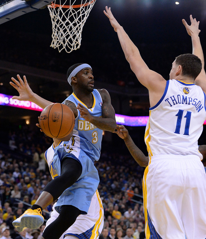 . Denver Nuggets point guard Ty Lawson (L) passes the ball around Golden State Warriors shooting guard Klay Thompson (R) during the first half of their NBA game at Oracle Arena in Oakland, California.  EPA/JOHN G. MABANGLO CORBIS OUT