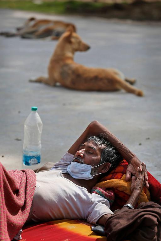 . In this Monday, Feb. 3, 2014 photo, tuberculosis patient Rama Shanker sleeps in the sun inside the complex of Lal Bahadur Shastri Government Hospital at Ram Nagar in Varanasi, India. (AP Photo/Rajesh Kumar Singh)