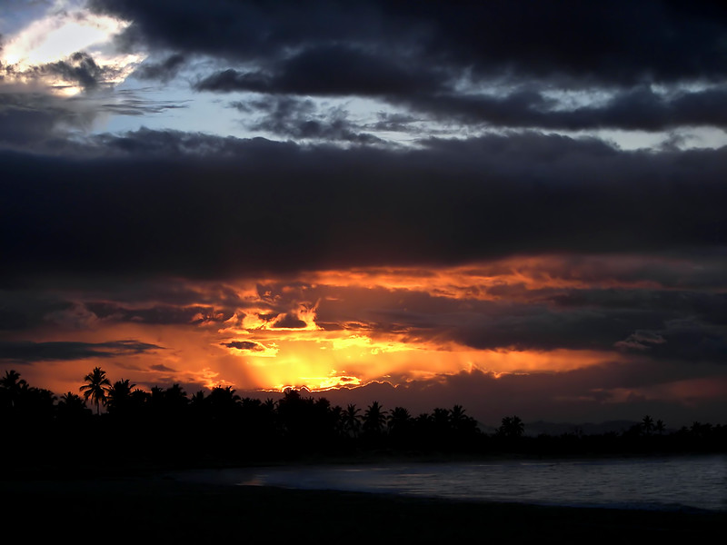 Photograph of a beautiful tropical sunset with a view of shoreline and waves breaking on the beach.