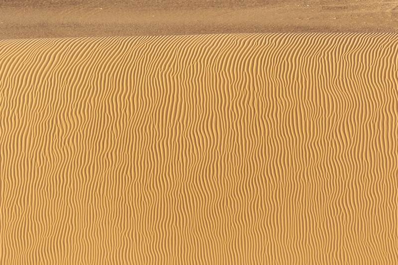A bedazzling pattern of vertical wavy lines runs down the side of a sand dune