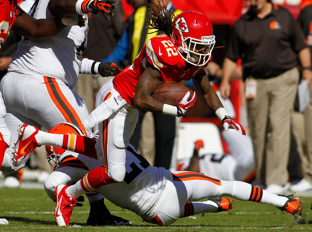 . Kansas City Chiefs wide receiver Dexter McCluster (22) is knocked down by Cleveland Browns cornerback Chris Owens (21) during the first half of an NFL football game in Kansas City, Mo., Sunday, Oct. 27, 2013. (AP Photo/Colin E. Braley)